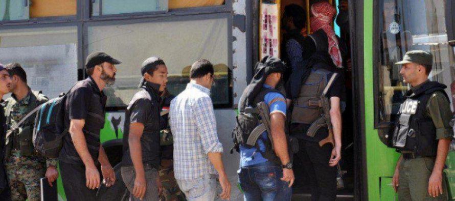 Grupo de armados y sus familias salen del barrio de Waaer, en Homs
